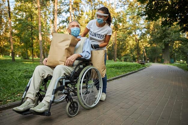 Vrouwelijke vrijwilliger helpt de volwassen gehandicapte man