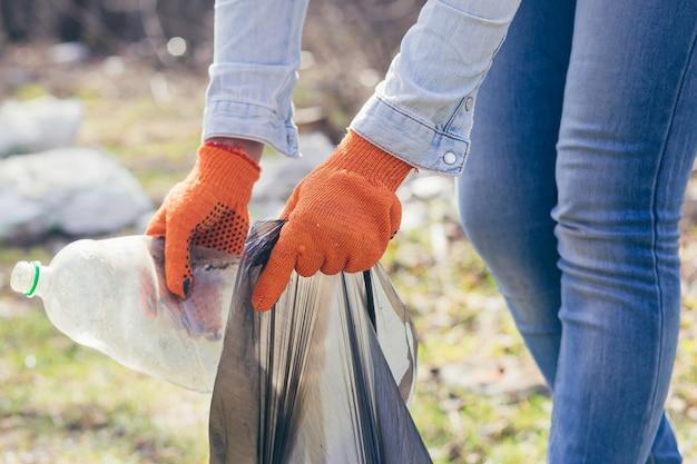 Vrouwelijke vrijwilliger houdt een zak met verzameld plastic vast die het bos en park schoonmaakt van vuilnis