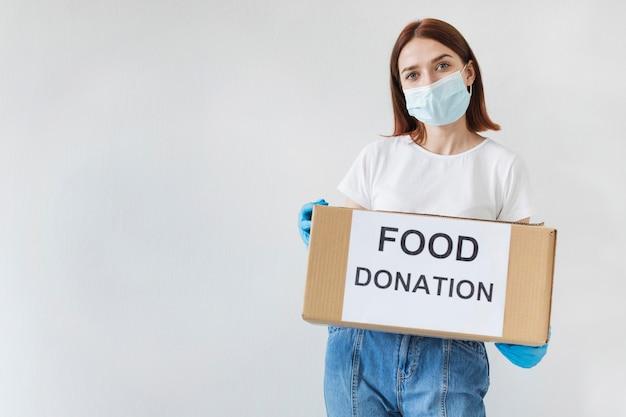 Vrouwelijke vrijwilliger met donatiebox met kopie ruimte