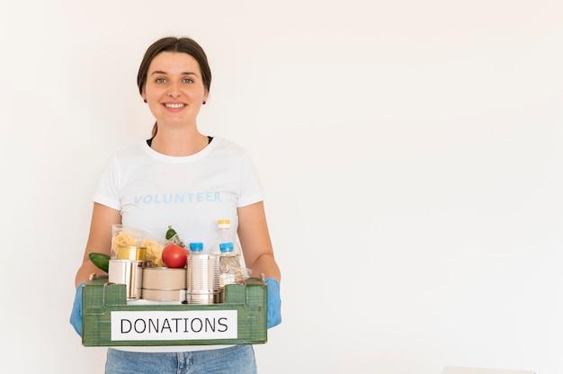 Vrouwelijke vrijwilliger met handschoenen die doos met voedseldonaties behandelen