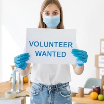 Vrouwelijke vrijwilliger met medisch masker en handschoenen die document met informatie houden