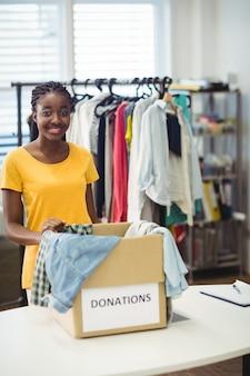 Vrouwelijke vrijwilliger staat met donatie doos