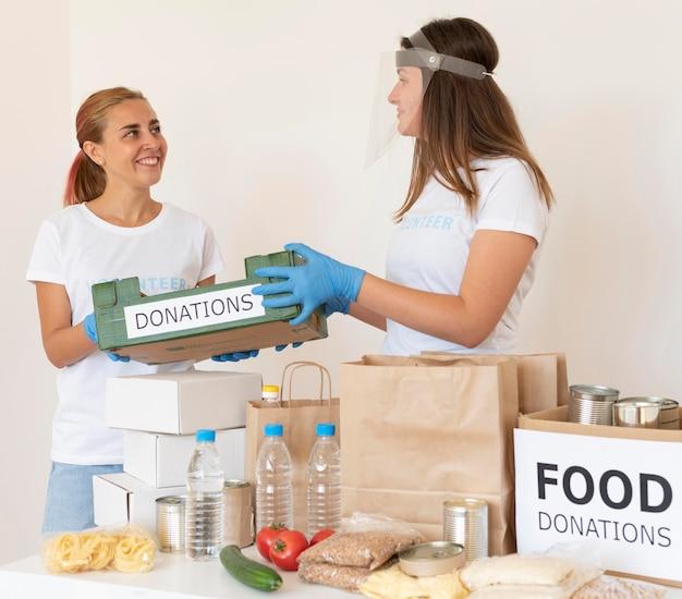Vrouwelijke vrijwilligers die dozen met voedseldonaties voorbereiden