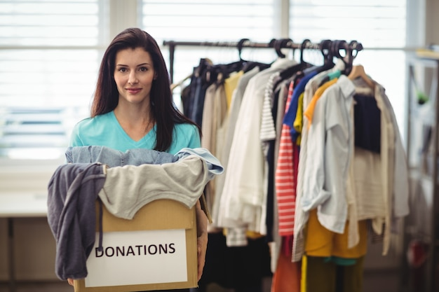 Vrouwelijke vrijwilligers houden kleren in donatie doos
