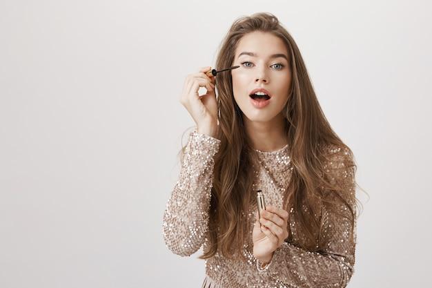 Vrouwelijke vrouw die zich klaarmaakt, mascara toepassen