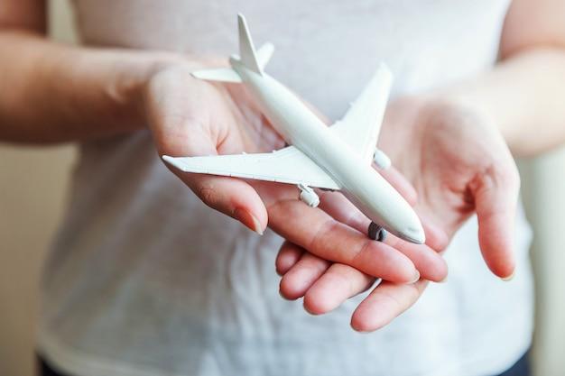 Vrouwelijke vrouw handen met klein speelgoed modelvliegtuig