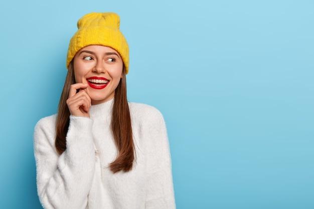 Vrouwelijke vrouw met donker haar, draagt rode lippenstift, draagt gele hoed en witte zachte trui, glimlacht breed, houdt de vinger bij de lippen, kijkt opzij, staat tegen een blauwe achtergrond.
