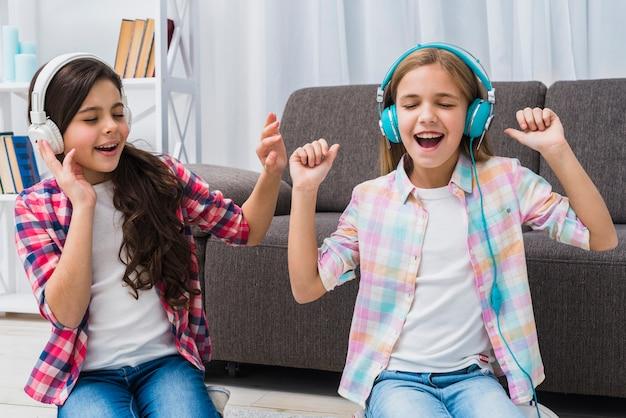 Vrouwelijke vrouw twee die van de muziek op hoofdtelefoon thuis geniet