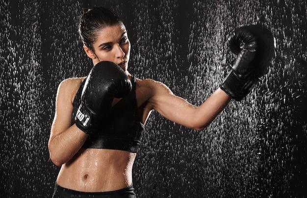 Vrouwelijke vrouw vechter 20s in sportkleding die sportoefeningen doet of in zwarte bokshandschoenen oefent terwijl hij stoten onder regendruppels gooit, die over donkere achtergrond worden geïsoleerd