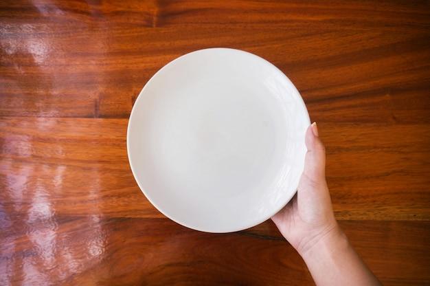 Vrouwelijke (vrouwelijke) handen houden (steun) een witte schotel (bord) op houten tafel.