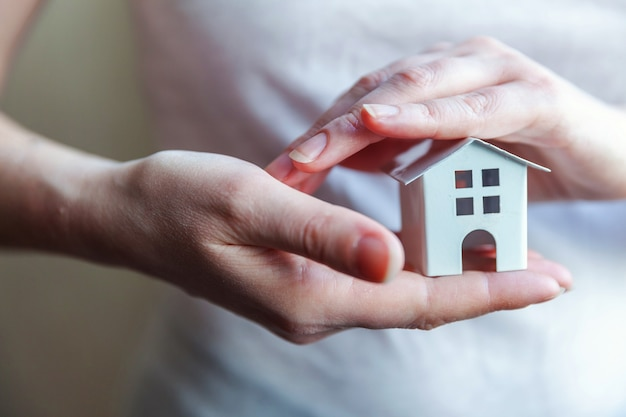 Vrouwelijke vrouwenhanden die miniatuur wit stuk speelgoed huis houden