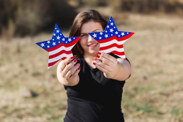 Vrouwelijke vs vlag sterren houden en camera kijken