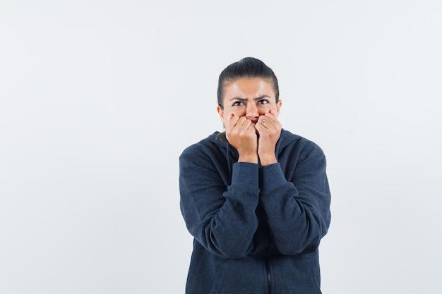 Vrouwelijke vuisten emotioneel bijten in hoodie en bang op zoek. vooraanzicht.