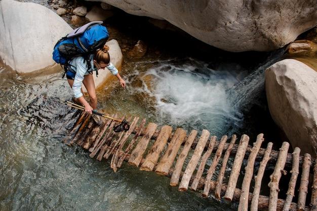 Vrouwelijke wandelaar die door rivier tussen klippen waden
