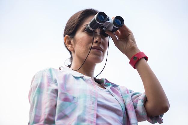 Vrouwelijke wandelaar die door verrekijkers kijkt