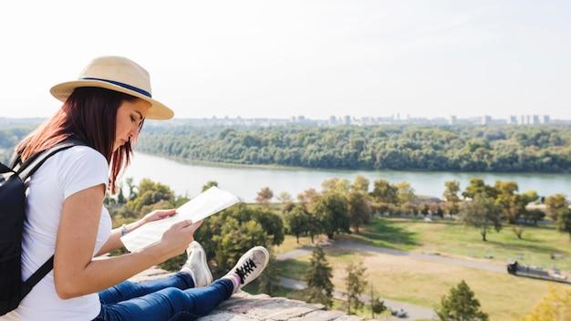 Vrouwelijke wandelaar die in kaart in openlucht eruit ziet