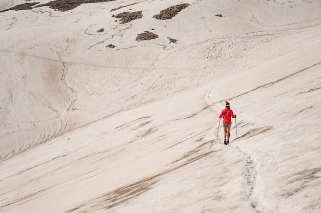 Vrouwelijke wandelaar die met wandelstokken in bergen reizen