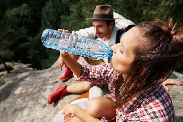 Vrouwelijke wandelaar drinkwater in de bergen