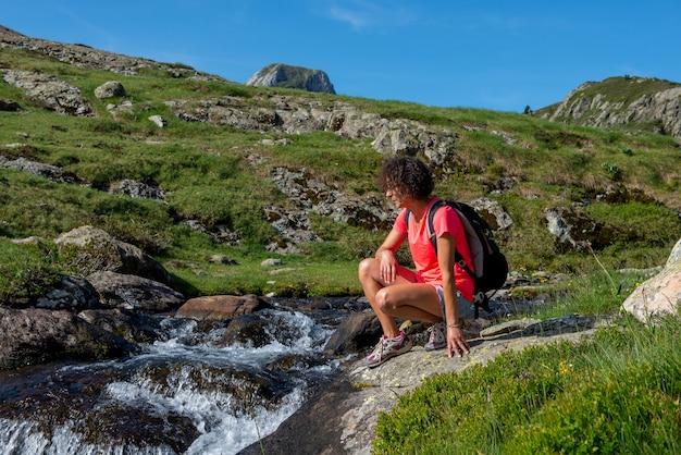 Vrouwelijke wandelaar hurken in de buurt van wilde spatten waterval