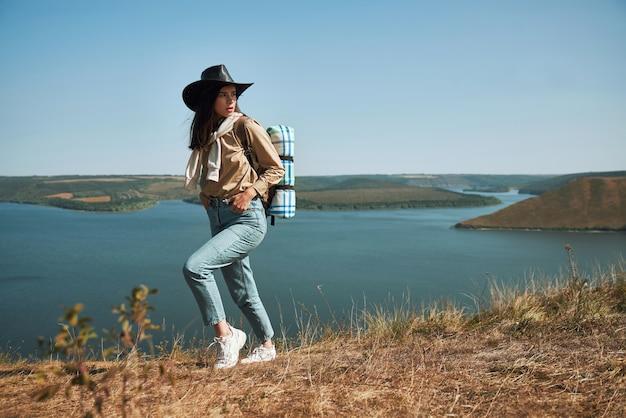 Vrouwelijke wandelaar in cowboyhoed wandelen met rugzak
