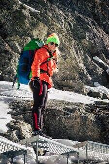 Vrouwelijke wandelaar klimmen naar de rysy-bergtop in de winter