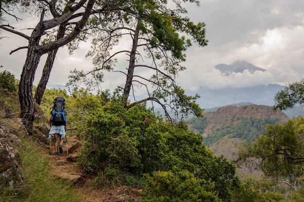 Vrouwelijke wandelaar met rugzak die in heuvels reist