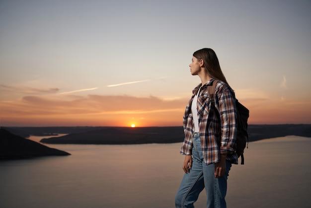 Vrouwelijke wandelaar met rugzak die prachtige zonsondergang bewondert