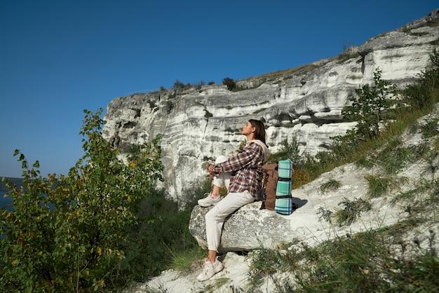 Vrouwelijke wandelaar met rugzak zittend op rots