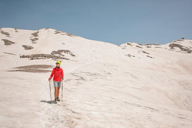 Vrouwelijke wandelaar met wandelstokken in bergen