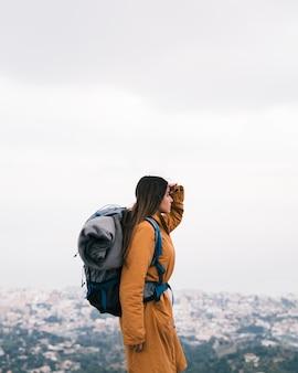 Vrouwelijke wandelaar met zijn rugzak die mening bekijkt