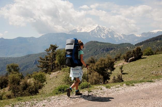 Vrouwelijke wandelaar reist over de weg in heuvels