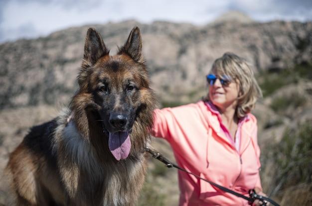 Vrouwelijke wandelaar rusten met haar hond en genieten van de frisse lucht