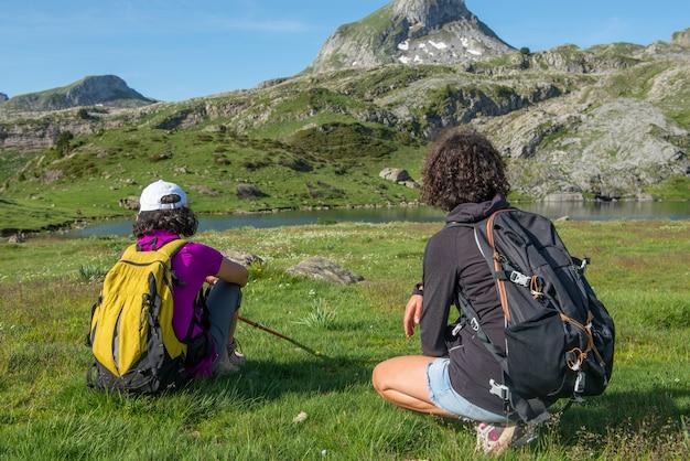 Vrouwelijke wandelaars die in de berg rusten