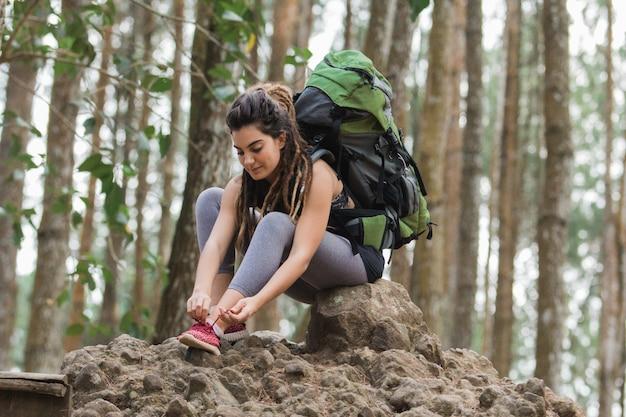 Vrouwelijke wandelaars dragen een rugzak die aan schoenveters is vastgemaakt