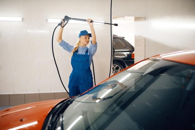Vrouwelijke wasmachine in uniform reinigt de auto met hogedrukpistool in handen