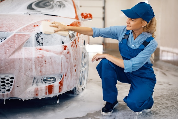 Vrouwelijke wasmachine met spons veegt de koplampen van de auto af