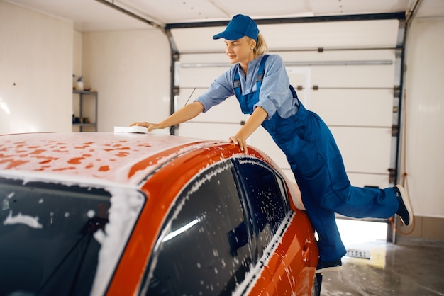 Vrouwelijke wasmachine met spons veegt de voorruit van de auto af