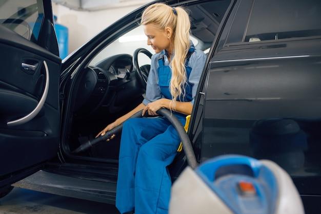 Vrouwelijke wasmachine met stofzuiger reinigt auto-interieur, wasstraat.