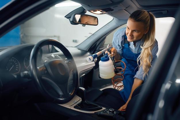 Vrouwelijke wasmachine reinigt auto-interieur