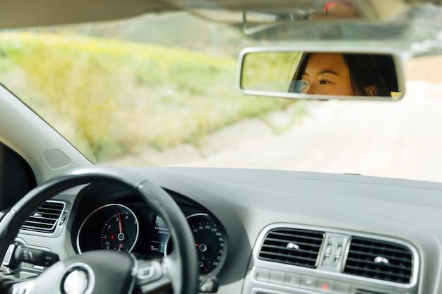 Vrouwelijke weerspiegeling in autospiegel