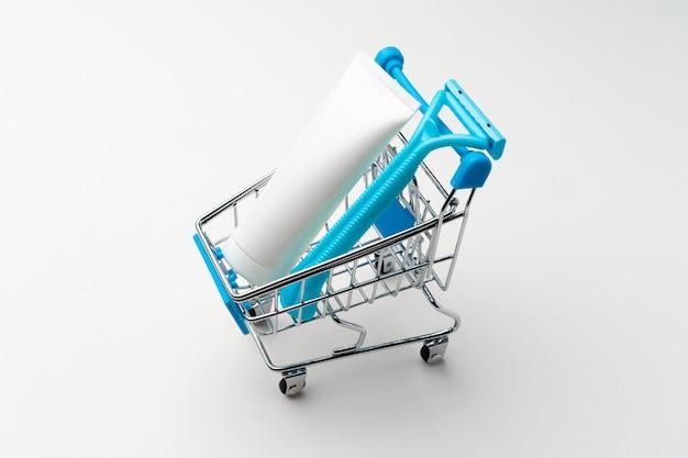 Vrouwelijke wegwerp scheerapparaat in speelgoed winkelwagentje op witte achtergrond close-up
