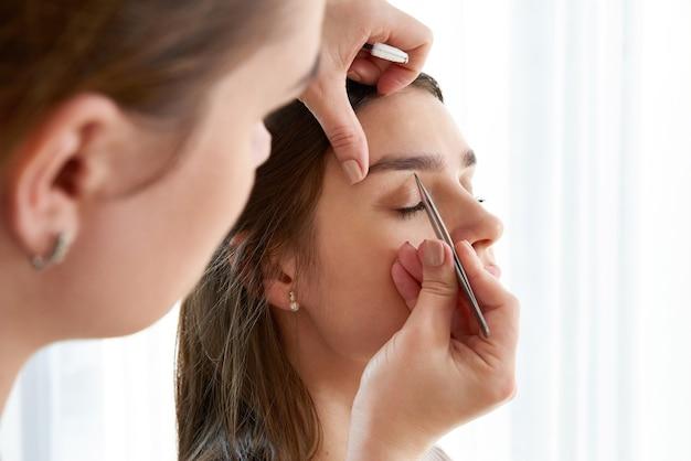 Vrouwelijke wenkbrauwen plukken met een pincet tijdens wenkbrauwcorrectie in de schoonheidssalon