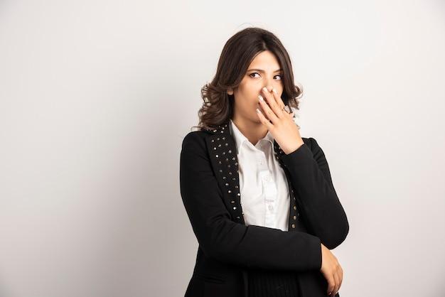 Vrouwelijke werknemer bedekt haar mond vanwege plotseling nieuws