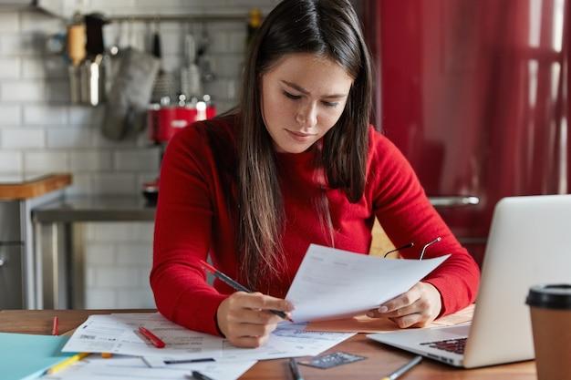 Vrouwelijke werknemer bestudeert marktanalyse, maakt financiële prognoses, vormt op de werkplek met documentatie, elektronisch apparaat, werkt op keuken.