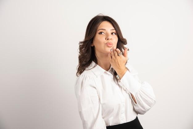 Vrouwelijke werknemer blaast kus op wit.
