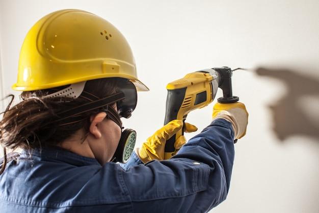 Vrouwelijke werknemer boort de muur, hard werken voor vrouwen
