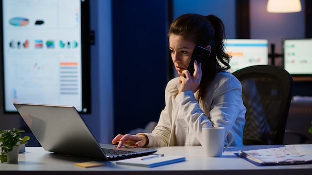 Vrouwelijke werknemer die aan de telefoon spreekt terwijl hij 's avonds laat op een laptop werkt. drukke, gefocuste freelancer die gebruik maakt van moderne technologienetwerken die overuren maken voor het lezen van een baan, schrijven, zoeken en pauze nemen
