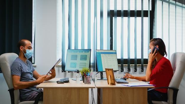 Vrouwelijke werknemer die een beschermingsmasker draagt, zit in een nieuwe normale kantoorruimte en bespreekt telefonisch met de bedrijfsleider. freelancer die op de werkplek werkt en schrijft op het klembord, zoekt op de computer