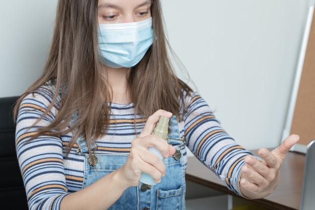 Vrouwelijke werknemer die elementaire ontsmettingshulpmiddelen gebruikt om het kantoor steriel te houden
