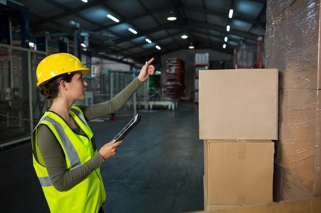 Vrouwelijke werknemer die in fabriek werkt